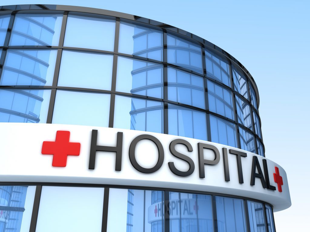 "The front of a hospital with the sign which reads, ""hospital."""
