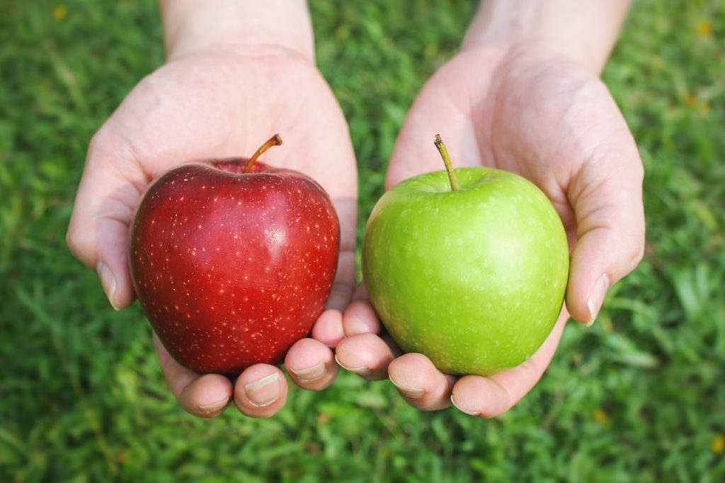 A red and a green apple held in two hands.