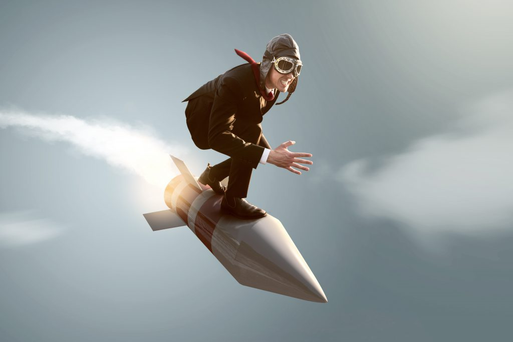 A business man representing iBuyers crouches on top of a fast rocket as they fly through a gray sky.
