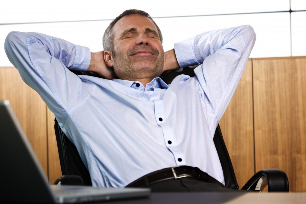Businessman/real estate appraiser in blue shirt, smiling, with his hands behind his head as he leans back in an office chair, not worried about iBuyers.