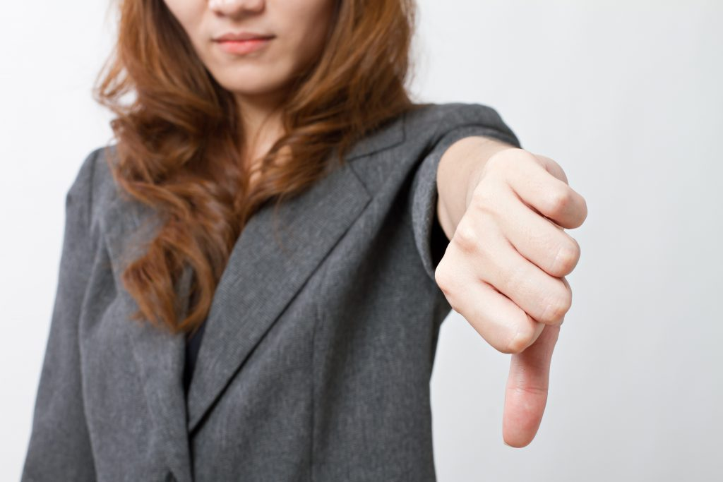 Business woman/real estate appraiser, dressed in gray suit puts her thumb down against iBuyers.
