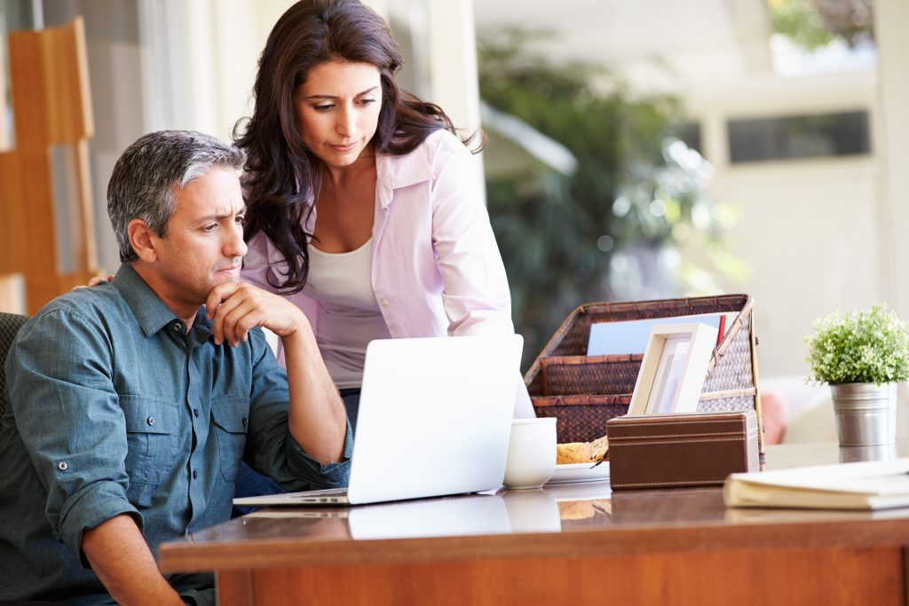 Worried man and woman stare at a laptop on a desk in a home office. They are worried about the impact of iBuyers, including Zillow, on their real estate appraisal business.