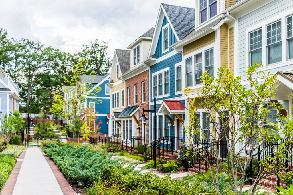 Row of colorful, red, yellow, blue, white, green painted residential townhouses, homes. They affect each other's appraisal value.
