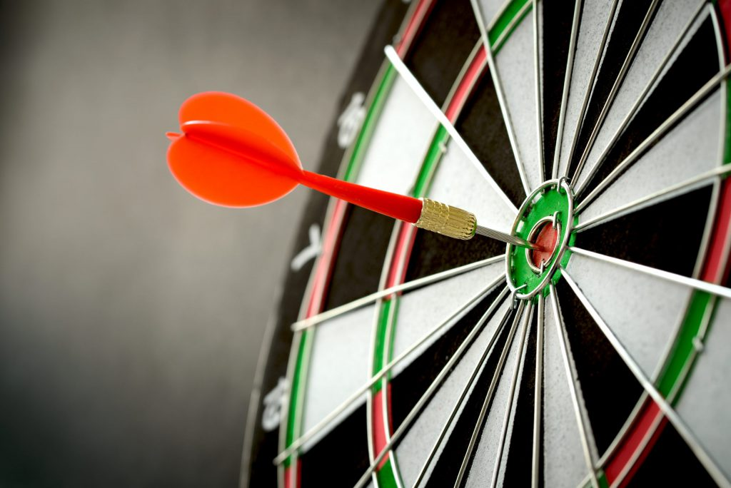 A red dart and a bulls eye on a target.
