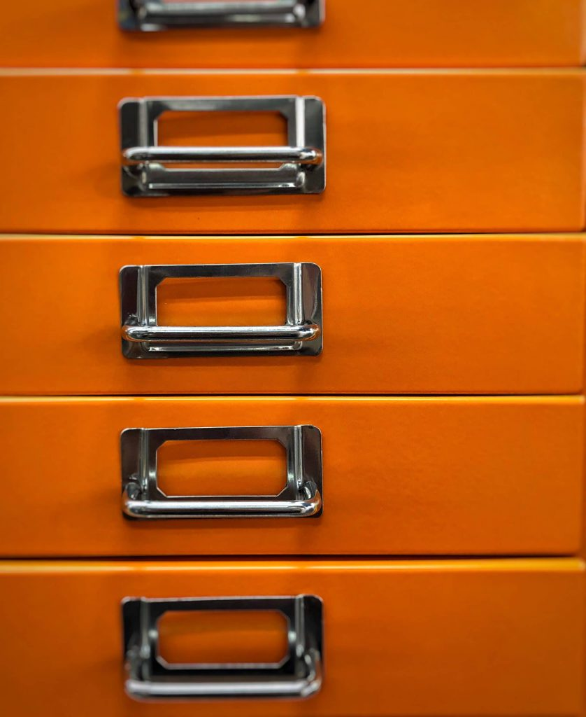 Orange Filing Cabinet with five silver metal handles.